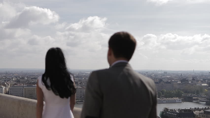 Young beautiful couple. A man walking to his woman and hug her, Budapest city skyline in background   Shutterstock HD Video #1013468897