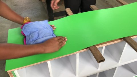 Cabinet makers applying formica to build shoe rack closets