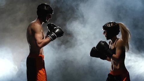 Girl boxer is coached by a man. Boxing sparring in the ring. Slow motion. Smoke background