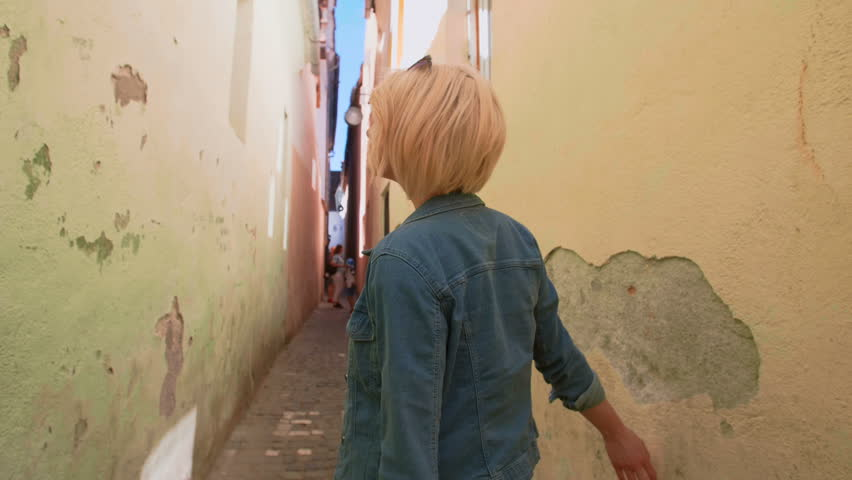 Young woman posing on a very narrow city street | Shutterstock HD Video #1013494937