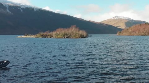 Small Boat Scottish Loch, small outboard engine, Winter/Autumn Snow on Mountains