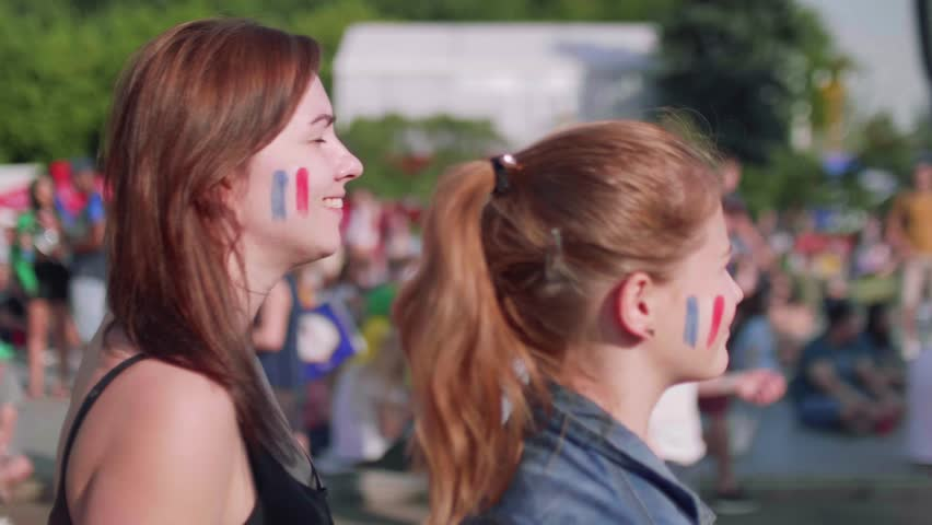 Two female fans cheer for French team while football match. Side view   Shutterstock HD Video #1013519897
