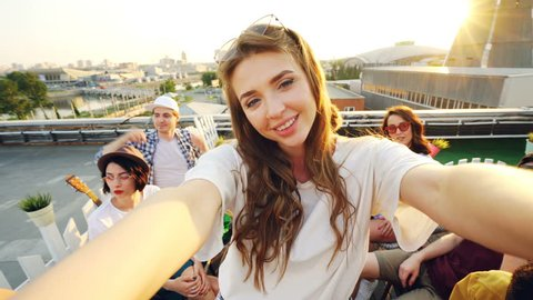 Attractive young woman is taking selfie with friends on rooftop, girl is holding camera and posing while her mates are having fun making funny faces and gestures.