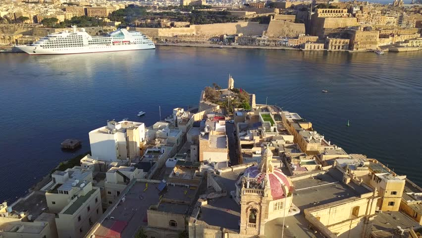 Senglea, Malta - 4K flying above Gardjola Gardens, Senglea and Grand Harbour with Valletta and cruise ship at background at sunrise | Shutterstock HD Video #1013550857
