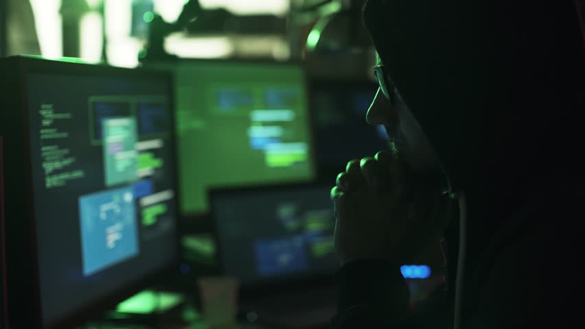 Nerd hacker with hoodie working at desk late at night, he is watching multiple screens and hacking networks, cyber security concept | Shutterstock HD Video #1013574437