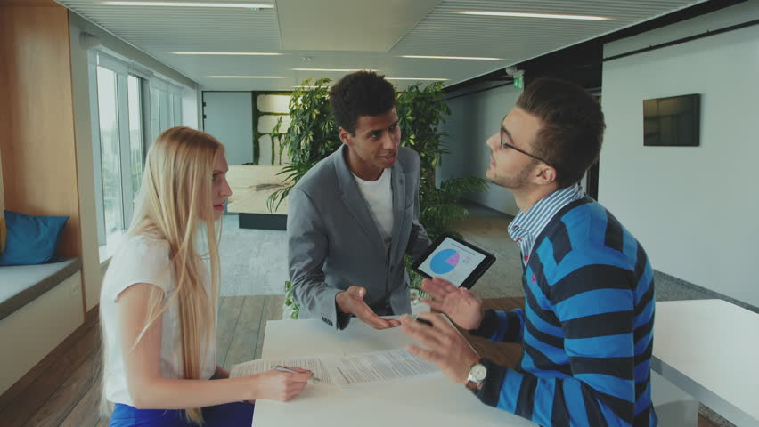 Multiracial men and woman working on report. Group of diverse woman and men with tablet in modern office hall having work with documents and statistics. | Shutterstock HD Video #1013575667