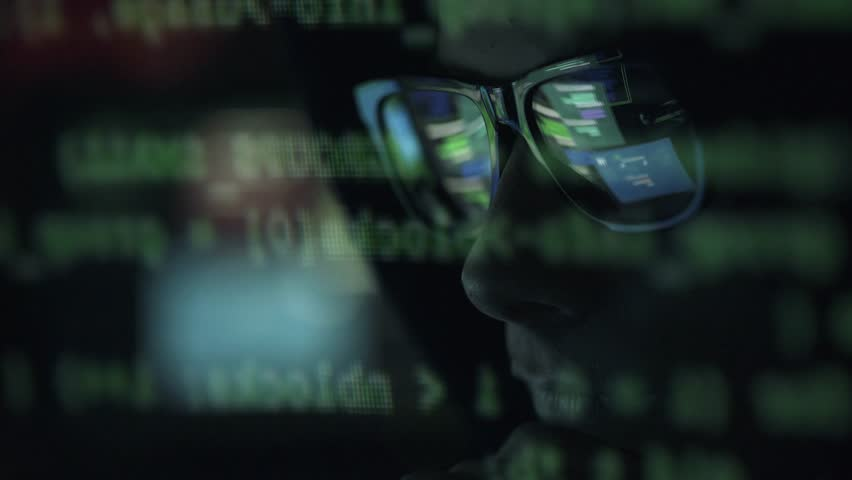 Young nerd hacker with glasses connecting online and stealing data, cyber crime and hacking concept
