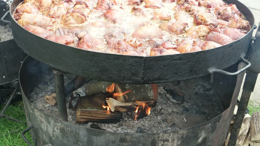 Pork legs stew in a large skillet.  Festival of Ukrainian   national cuisine in the open- air, Ivano-Frankivsk, Ukraine