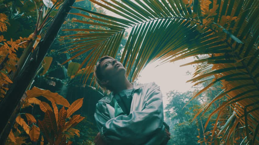 Beautiful fashion girl posing in tropical rain forest jungle near the waterfall. Portrait of stylish hipster female outdoor | Shutterstock HD Video #1013600507