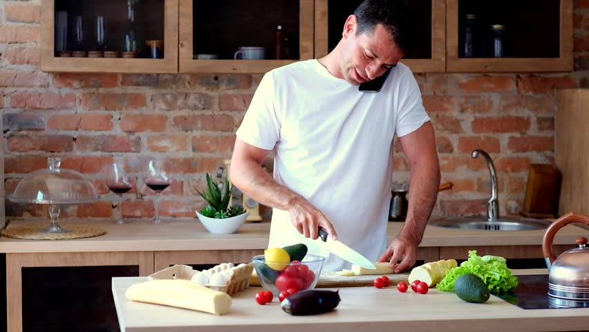 Young attractive man cutting cheese and talking on the phone in the kitchen | Shutterstock HD Video #1013603837