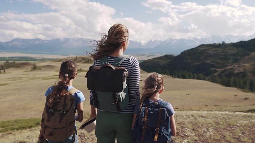 Tourists in the mountains. a young mother and her daughters teenagers in a hike. woman with children admiring the stunning views of the mountains | Shutterstock HD Video #1013629187
