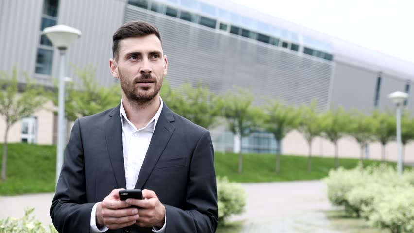 Portrait of Young Handsome Office Worker. Walking along the Park Alley. Chatting on his Modern Smartphone.  | Shutterstock HD Video #1013630777