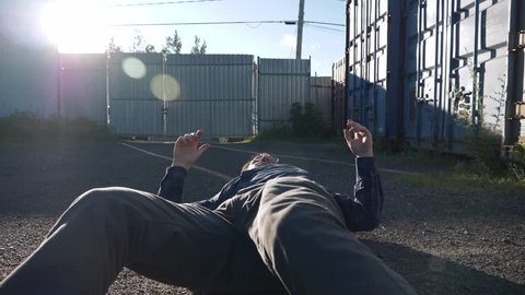 Camera rotating around a male worker on the ground right after a heart stroke or another medical condition. He is looking lost and shaking his arms.