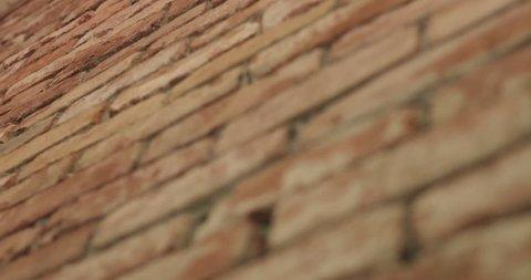 Slow motion handheld closeup pan of filled seams on brick wall
