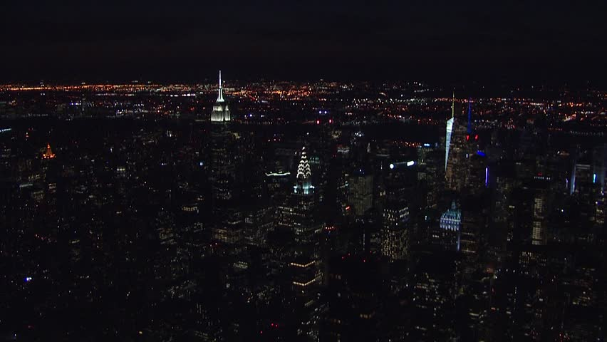 Wide NX aerial establishing shot overhead midtown manhattan at night. Skyline buildings and skyscrapers light up illuminate night sky and traffic on busy New York City streets | Shutterstock HD Video #1013668547