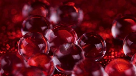 Crystal Gel water balls on red glitter texture rotation. Close up macro footage.