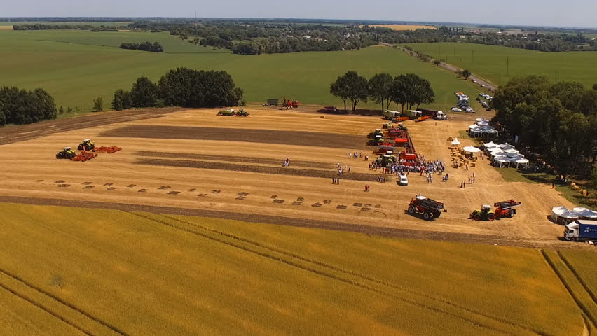 Aerial footage. Exhibition of modern agricultural machinery from a bird's eye view. Combines, tractors, seeders, sprayers, harrows #1013670647