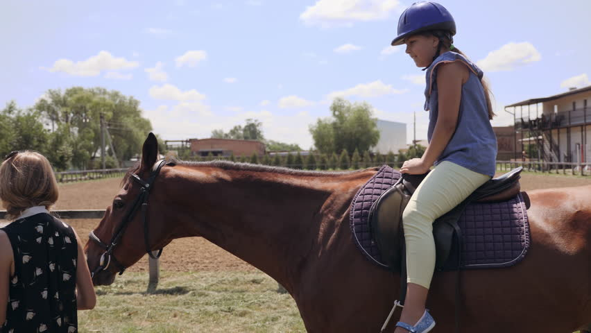 Side view. Hippotherapy rehabilitation deals with child riding on horseback. Communication with horses | Shutterstock HD Video #1013677007