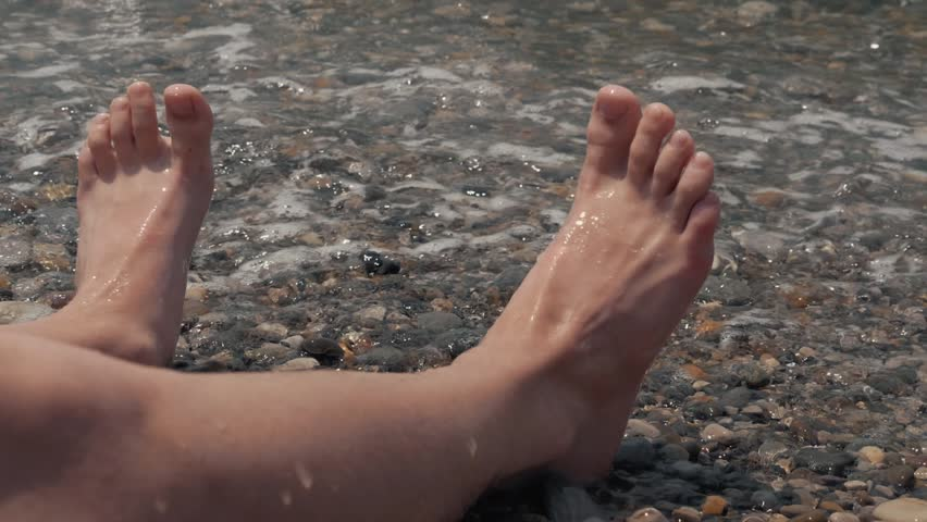 A close-up of a child's legs is overwhelmed by a wave. Pebble sea beach noisy sea waves on children's legs | Shutterstock HD Video #1013679017