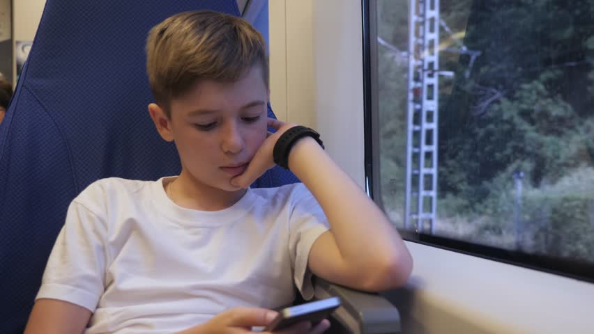 A boy with a smartphone in his hands travels by train and communicates with his friends via the Internet | Shutterstock HD Video #1013684237