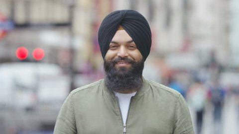 Portrait of young Indian male wearing a turban and smiling to camera, in slow motion