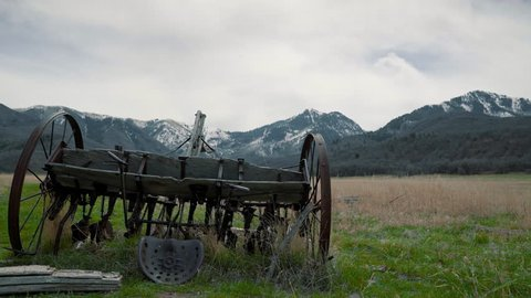 An old rusty abandoned horse plow sitting in a meadow with the rocky mountains in the background