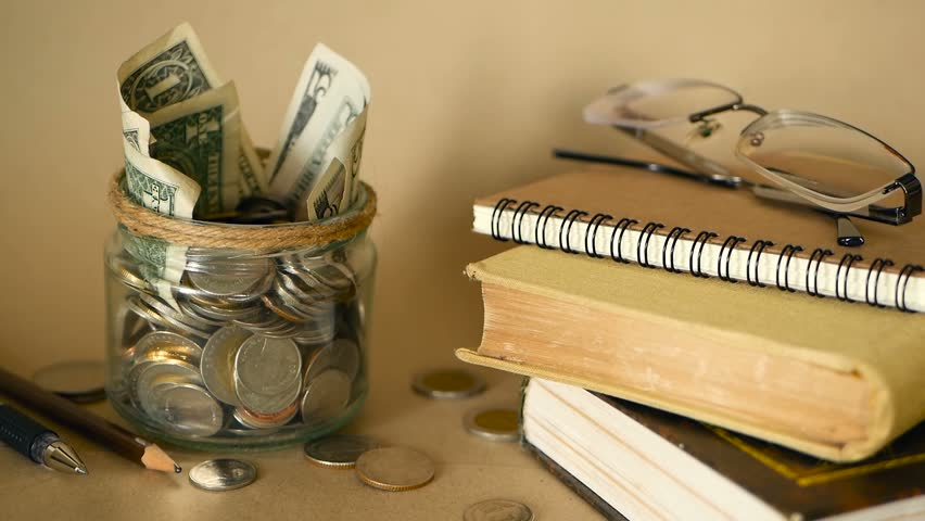 Books with glass penny jar filled with coins and banknotes. Tuition or education financing concept. Scholarship money. Savings for future education. Books, glasses, clock in background. Soft focus   Shutterstock HD Video #1013729747