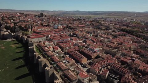 Aerial view of the ancient center of Avila, Spain. Drone flies over the 2516 meters long defensive town walls with semicircular towers, the old town within the walls and a modern road surrounding them