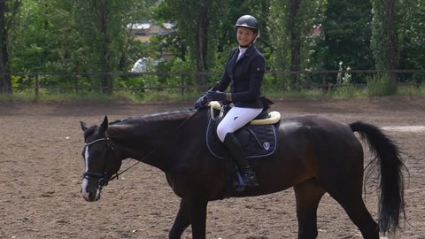 A young girl rider rides a horse on horseback sitting in the saddle and strokes the horse around the neck. Dressage training