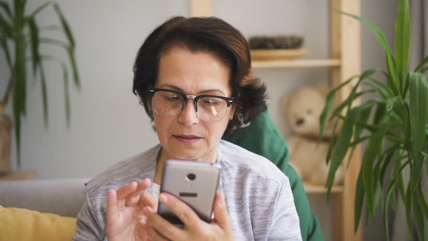 Senior concentrated woman in glasses writing message on her brand-new smartphone sitting on the sofa with yellow pillow at home. Indoors. Portrait. Straight shot. | Shutterstock HD Video #1013757227