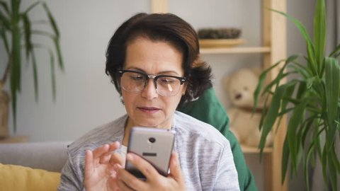 Senior concentrated woman in glasses writing message on her brand-new smartphone sitting on the sofa with yellow pillow at home. Indoors. Portrait. Straight shot.