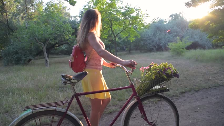 Young female with bicycle walking in park | Shutterstock HD Video #1013795327