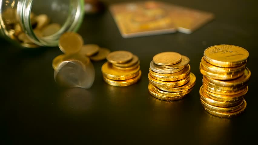 Saving money coin from jar. Symbol of investing, keeping money concept. Collecting cash conis in glass tin as moneybox. Close-up still life with increasing columns of gold coins on black table   Shutterstock HD Video #1013797967