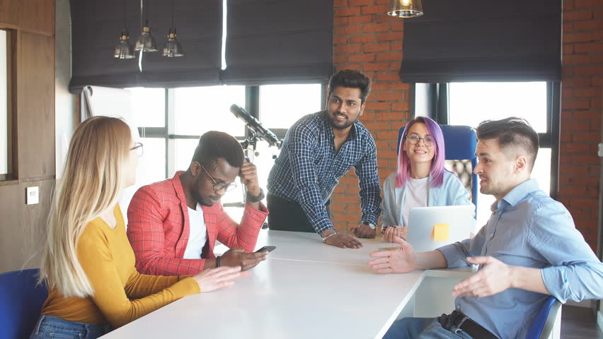 Well-known female designer with violet dyed hair visiting company of young designers. Business People of different races meeting at modern office to discuss developing strategy   Shutterstock HD Video #1013799977