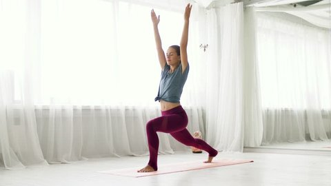 fitness, sport and healthy lifestyle concept - woman making high lunge exercise at yoga studio