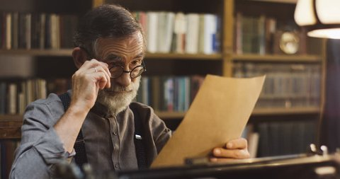 Portrait shot of the senior man in glasses holding an old paper sheet in a hand and reading it. At the library.