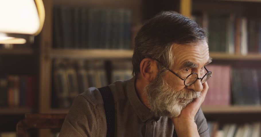 Portrait of the senior man in glasses sitting in the library and thinking while leaning on his hand. | Shutterstock HD Video #1013806457