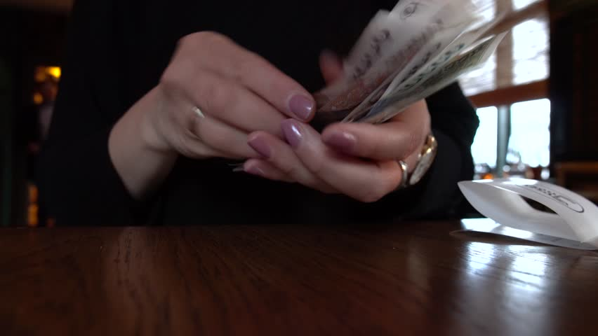 Woman counting Icelandic bills, paper money, cash on the table   Shutterstock HD Video #1013808077
