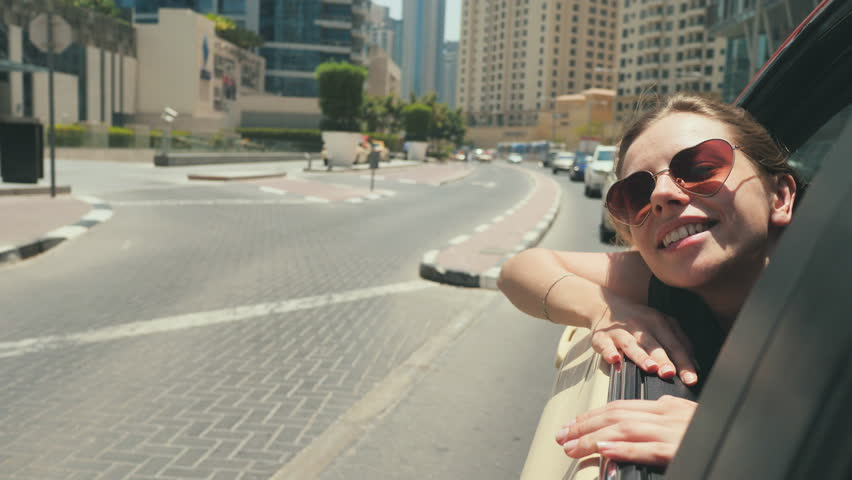 A happy girl sits on the back seat of a car and travels around the city of Dubai. | Shutterstock HD Video #1013811257