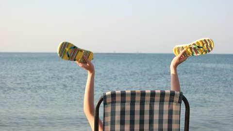 Woman sitting in chaise lounge and waving her flip flops. Back view, close up. Enjoying resort vacation at seashore.