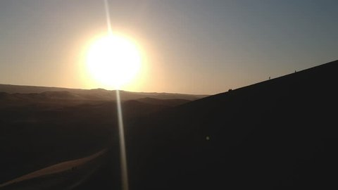 Aerial drone footage of a sunset above the sand dunes of Peru. Close to Ica and Huacachina oasis. Boogie cars driving and people sandboarding.
