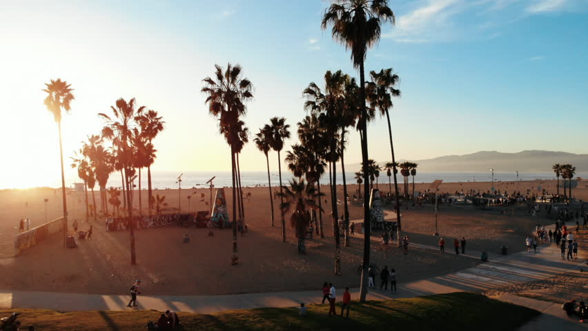Venice Beach Drone in Los Angeles, CA with beautiful sunshine during summer next to The Pier on the Beachfront with Skaters skating in the park