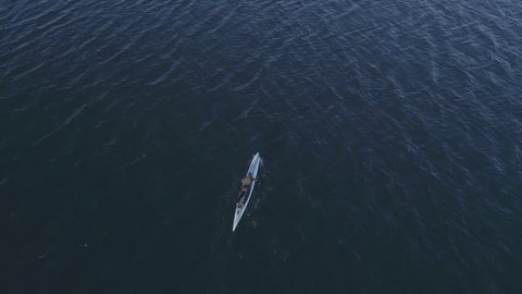 Aerial shot of person prone paddle boarding top view