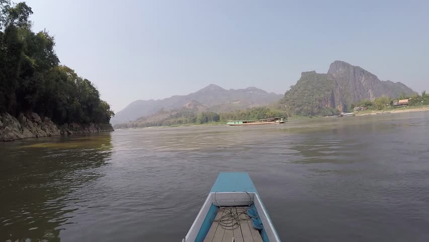 Crossing the Mekong river in a wodden banana boat near Pak Ou Caves north of Luang Prabang in Laos