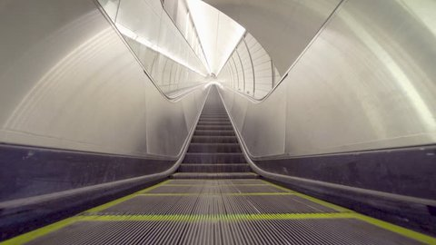 Empty long escalator moving to vanishing perspective. No people on modern architecture, lengthy, very high moving stairs in futuristic underground facility.