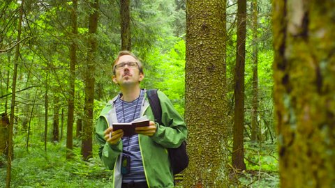 A scientist environmentalist exploring plants in a forest and writing data to a notebook