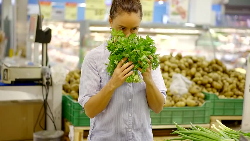 Woman is holding a bunch of fresh green herbs in a supermarket. | Shutterstock HD Video #1013886497
