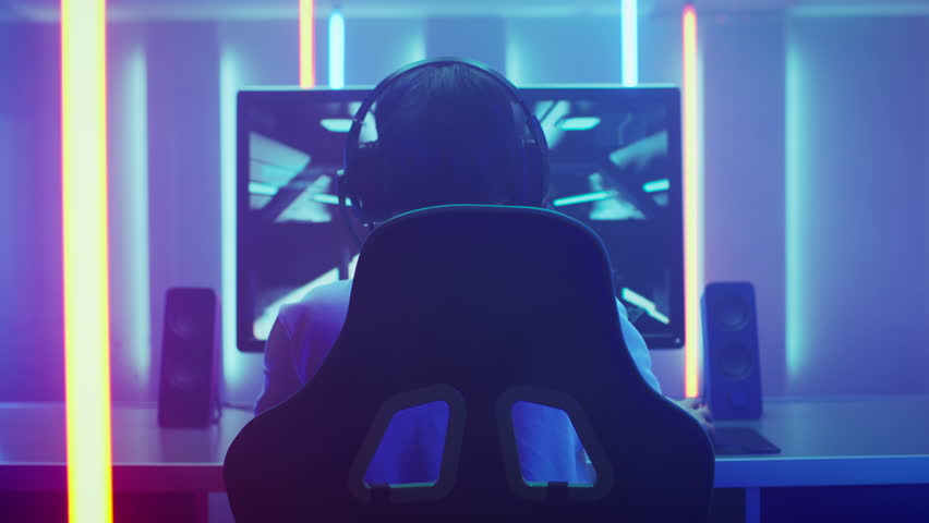 Back View Shot of the Professional Gamer Playing in First-Person Shooter Online Video Game on His Personal Computer. Room Lit by Neon Lights in Retro Arcade Style. Online Cyber e-Sport Championship. | Shutterstock HD Video #1013903807