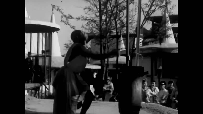 CIRCA 1960s - African men drum and dance at the 1964 New York World's Fair. A man arrives to the fair via amphibious car.