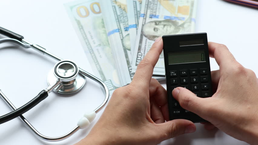 Counting medical costs using calculator, working desk, money and stethoscope in the background   Shutterstock HD Video #1013924027